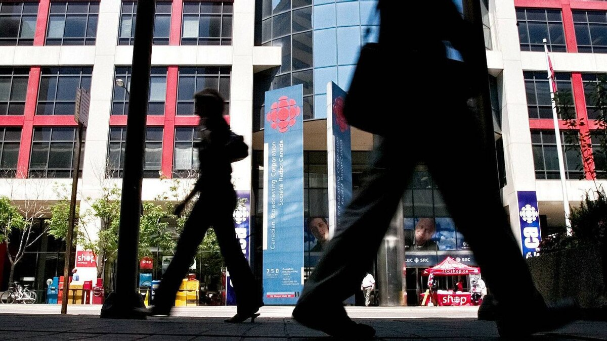 Pedestrians walk past the Canadian Broadcasting Corporation building in Toronto in June of 2006.