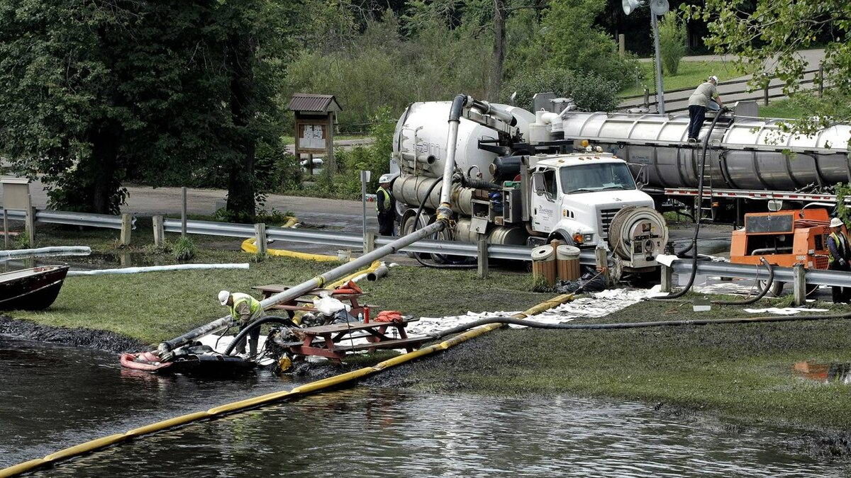 Workers using suction hoses try to clean up an oil spill this week from the Kalamazoo River in Battle Creek, Mich.