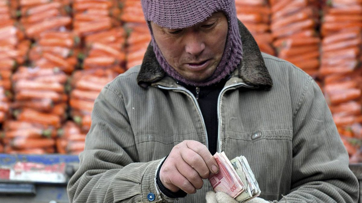 A man counts money in front of a truck loaded with carrots at a wholesale market in Fuyang in central China's Anhui province.