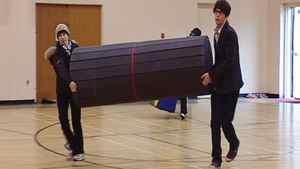 Go-Go Gymnastics staff Dana Butler and Wayne Fowler carry a floor mat into a school gym.