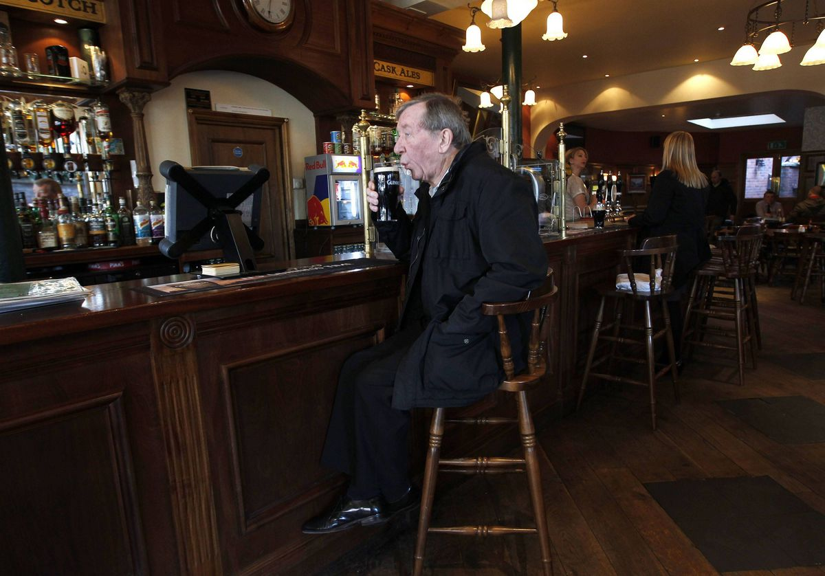 A customer takes a drink at Ye Olde Black Bull pub in east London. The building dates from 1892; however, there are records and an illustration of a pub of the same name on this site from the 17th century. In the 1970's England's World Cup winning captain Bobby Moore owned and renamed the pub Mooro's but it was burnt down the night before it was due to open.
