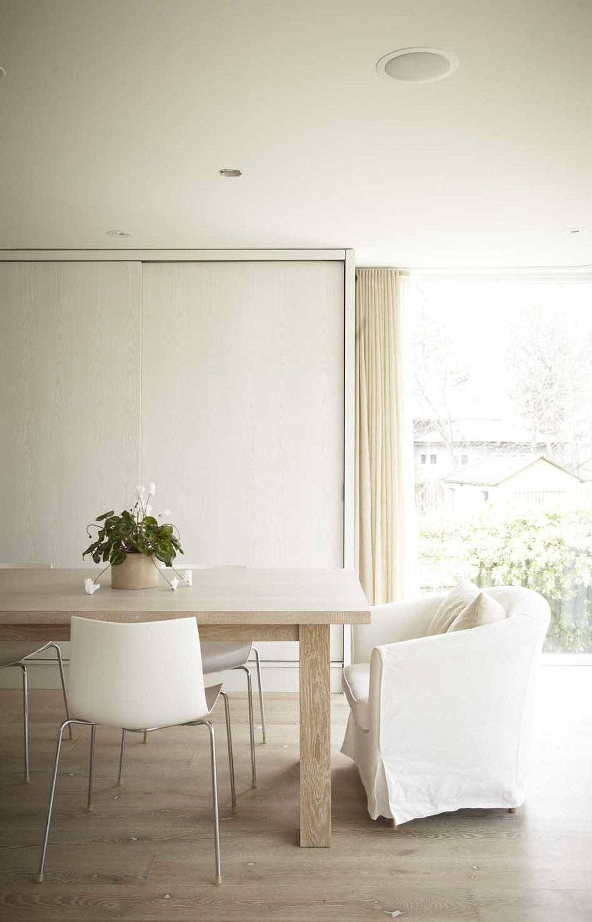 """The custom dining table is made from the same untreated white oak as the floors: """"The idea was to make it seem like it was melting into the floor,"""" Patsy Bell says."""