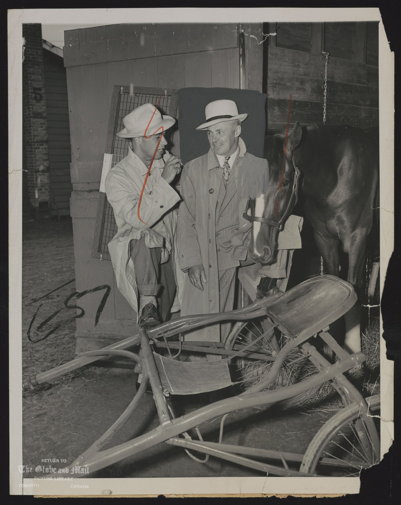 HAMBLETONlAN POSTPONED. WITH HIS SON, WILLIAM (LEFT), EARL ROWE, CANADIAN MEMBER OF PARLIAMENT, VISITS HIS ENTRY, VAN RIDDELL, IN THE BARNS OF GOOD TIME RACE TRACK AT GOSHEN, N. Y., AUG. 7 [1946]. THE 21ST RUNNING OF THE HAMBLETONlAN, SCHEDULED TO BE RUN AUG.7 WAS POSTPONED UNTIL AUG.8 BECAUSE OF HEAVY RAINS.