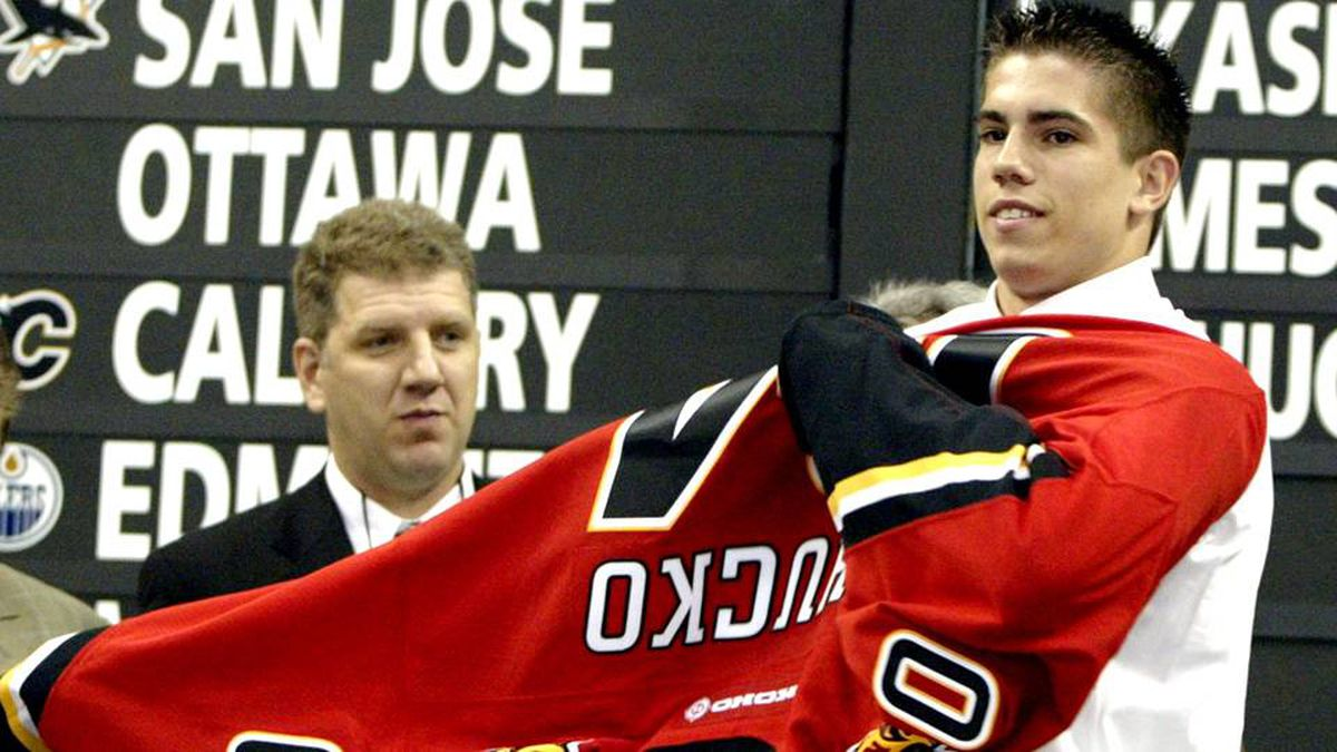 Kris Chucko of Burnaby, B.C. puts on the sweater of the Calgary Flames after being picked in the first round of the NHL draft, at the RBC Center In Raleigh, North Carolina, June 26, 2004.