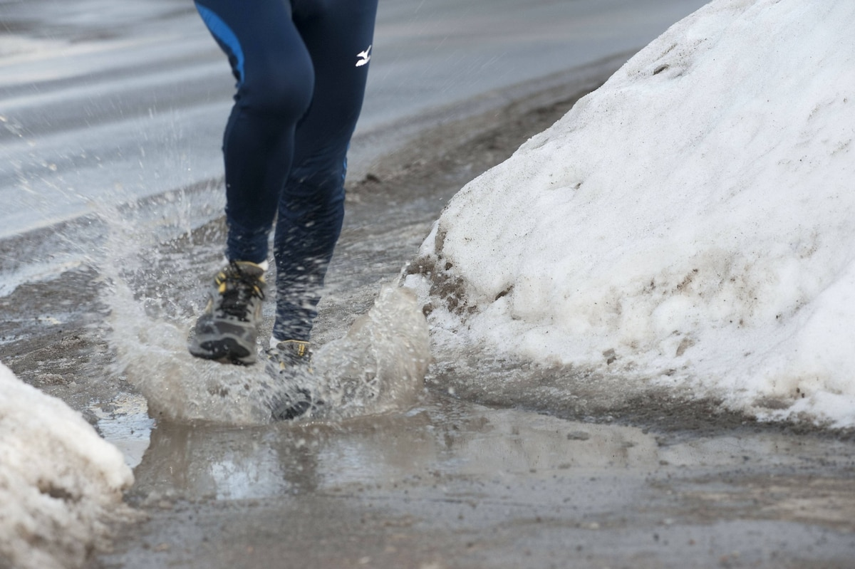 A runner negotiates a puddle during a run in Rothesay, New Brunswick on Thursday, February 17, 2011.