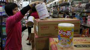 A staff member unpacks Japanese milk powder for a customer inside a store in Hong Kong March 16, 2011. Hundreds of people in the territory, worrying that future Japanese baby products will be contaminated by radiation, have lined up for milk powder. Radioactive materials spewed into the air by Japan's earthquake-crippled nuclear plant may contaminate food and water resources, with children and unborn babies most at risk of possibly developing cancer.