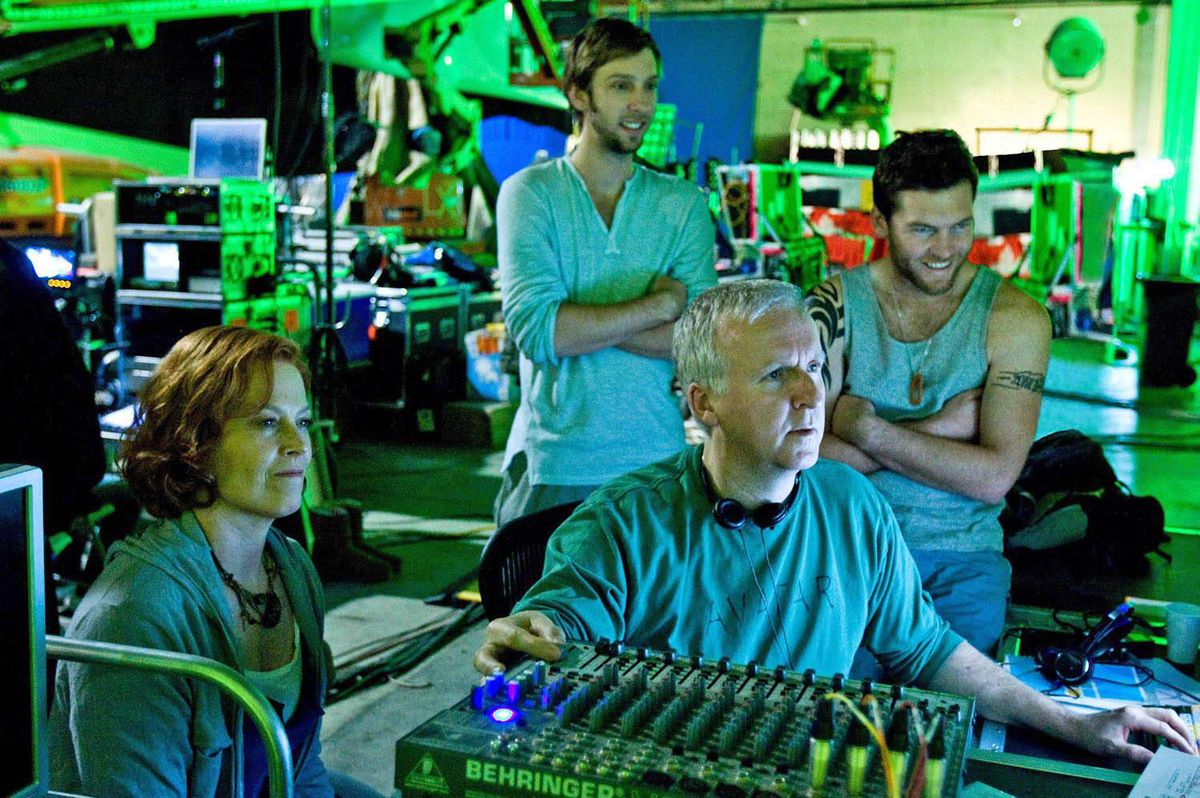 James Cameron (seated) reviews a scene with actors Sigourney Weaver, Joel David Moore and Sam Worthington.