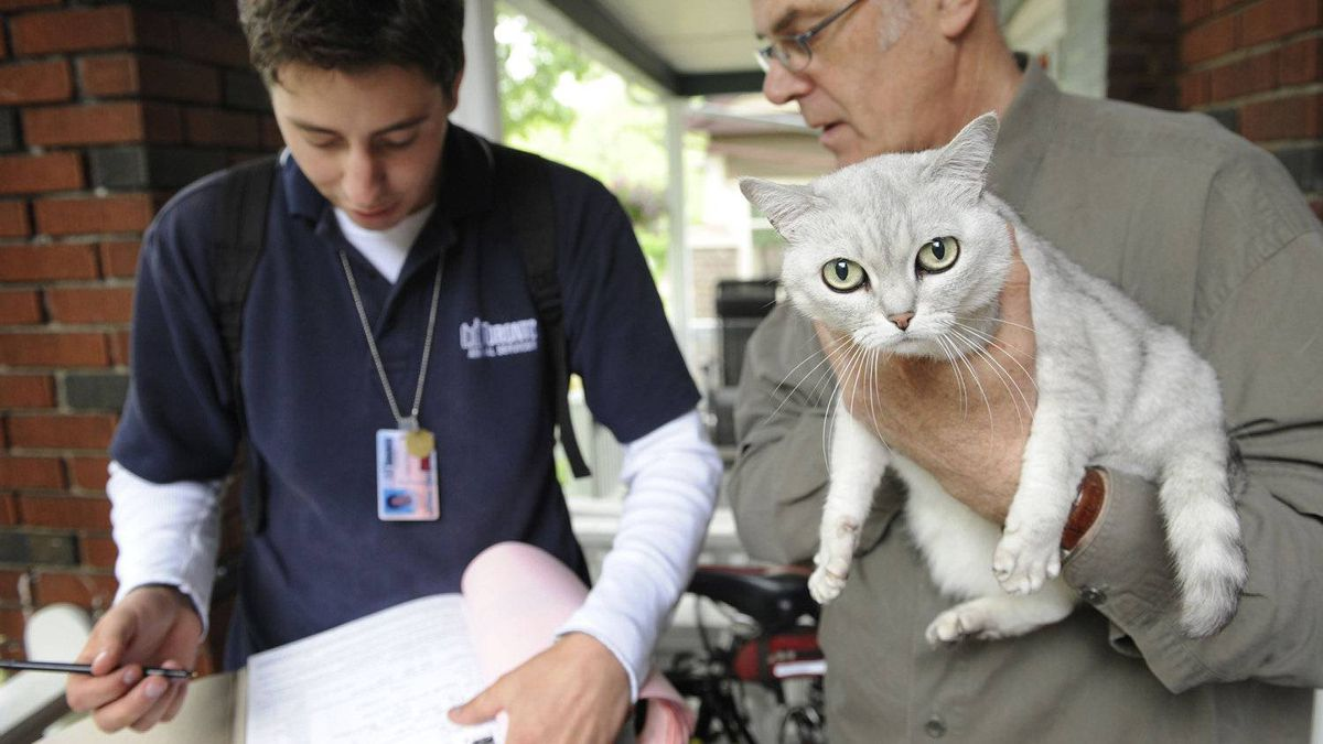 University student Jonathan Matson, left, speaks with Chris Terry and his cat Isis in this June 4, 2008 file photo. Mr. Matson was one of a number of students who went door to door for animal services to inform pet owners about the city's licensing.