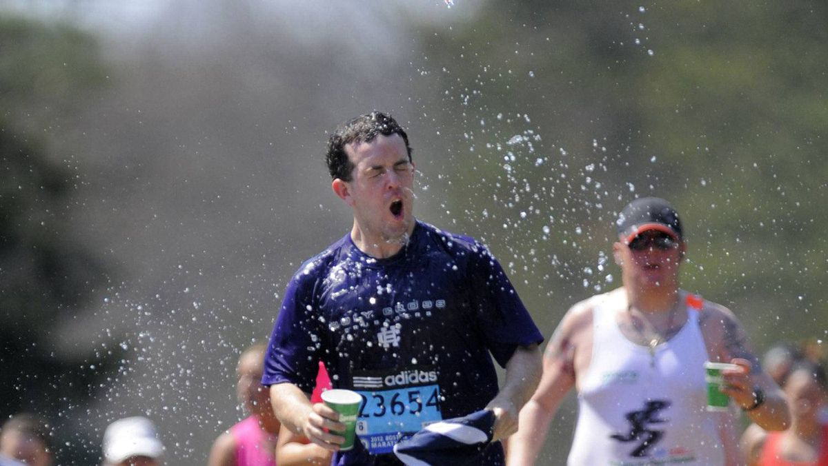 A runner douses himself with water along the route of the 116th Boston Marathon in Wellesley, Massachusetts April 16, 2012.