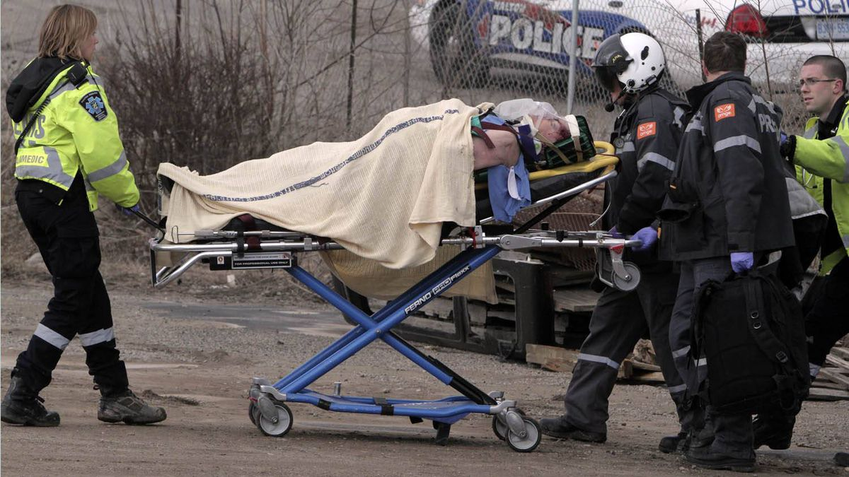 An injured passenger from a derailed Via train in Burlington is rushed to a waiting helicopter for medical evacuation Sunday February 26, 2012.