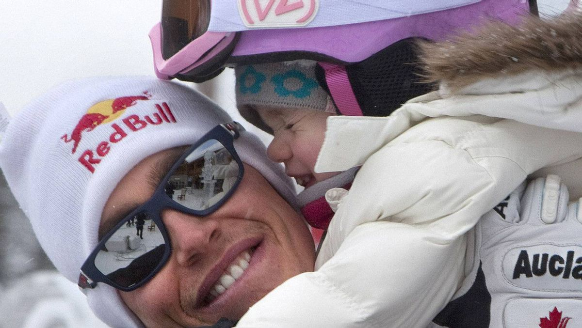 Erik Guay of Canada carries his 2-year-old daughter Logann following his alpine skiing training run at the Men's World Cup Downhill in Lake Louise, Alberta November 25, 2011. Guay placed second on the day. REUTERS/Andy Clark
