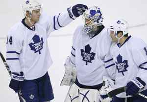 Toronto Maple Leafs forward Matt Stajan (L) and forward Lee Stempniak (R) console goalie Jonas Gustavsson after their loss to the Calgary Flames in their NHL hockey game in Calgary, January 2, 2010. REUTERS/Todd Korol