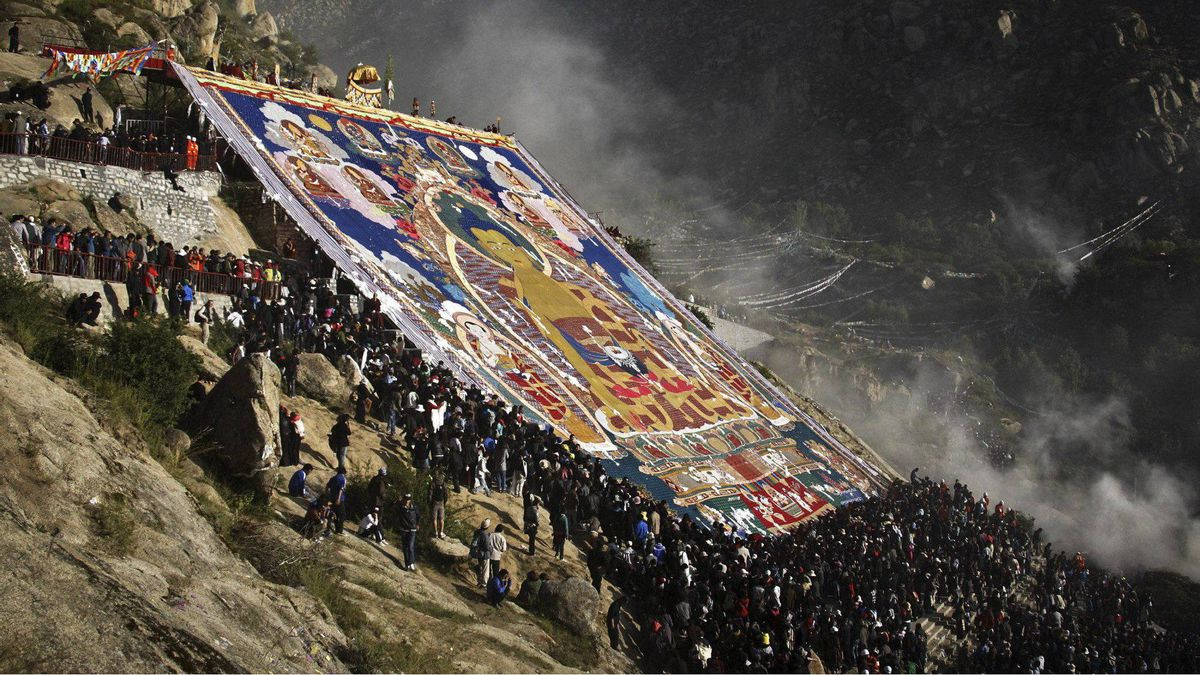 In this photo taken Monday, Aug. 29, 2011, Tibetans and tourists attend the unfolding ceremony of a giant thangka, a religious silk paintingy, as they celebrate the Tibetan Shoton Festival at the Drepung Monastery in Lhasa.