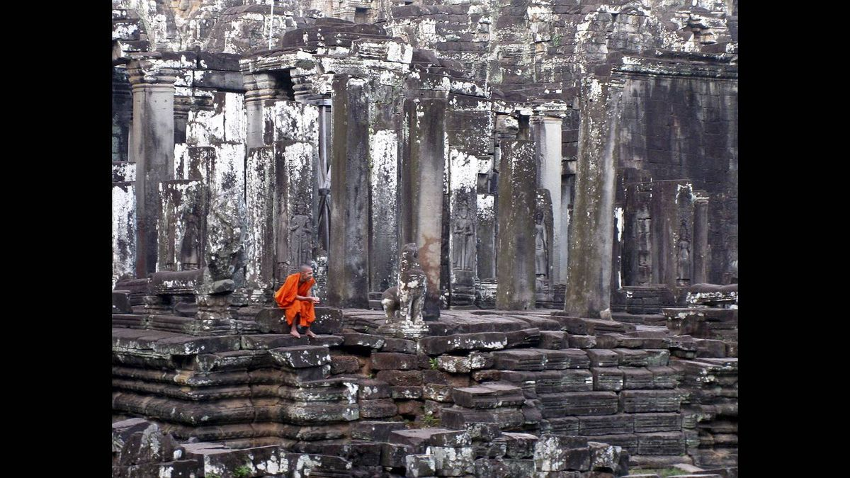 Chris McCloskey photo: Lost in Thought - This brightly-cloaked monk is in stark contrast to the walls of the ancient Angkor Thom temple near Siem Reap, Cambodia. Captured in January 2011 while on vacation there.