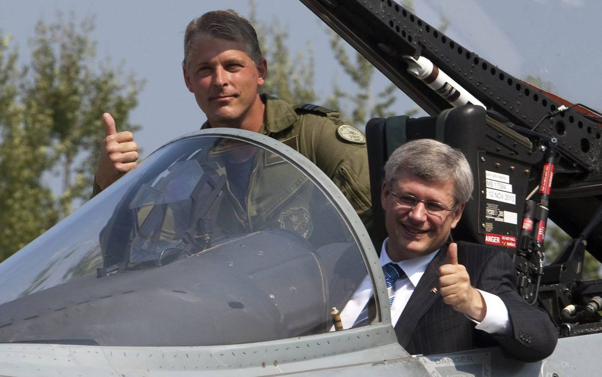 Prime Minister Stephen Harper sits in a CF-18 Hornet as Major Daniel Dionne explains the controls at the L-3 plant in Mirabel, Que., on Sept. 1, 2010.