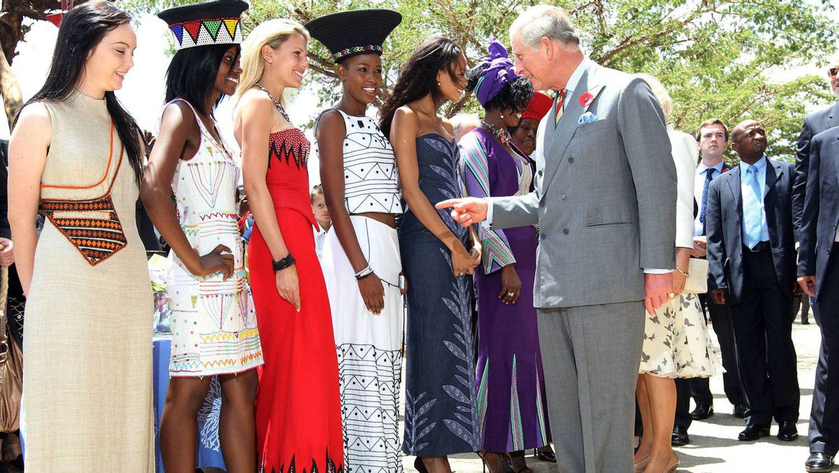 Britain's Prince Charles (R) greets models wearing clothing from a local designer during a tour of Soweto township, on November 3, 2011. The Prince and his wife, the Duchess of Cornwall, are due to visit Kwa Zulu Natal and Cape Town on a three day visit to South Africa before traveling to Tanzania.