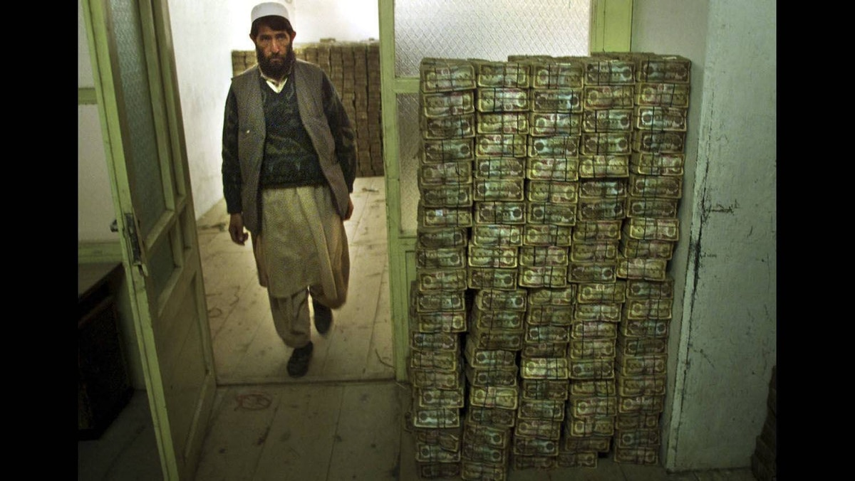 An Afghan man walks by stacks of worthless Afghani notes in an underground strongroom of the country's national bank in Kabul, November 29, 2001.