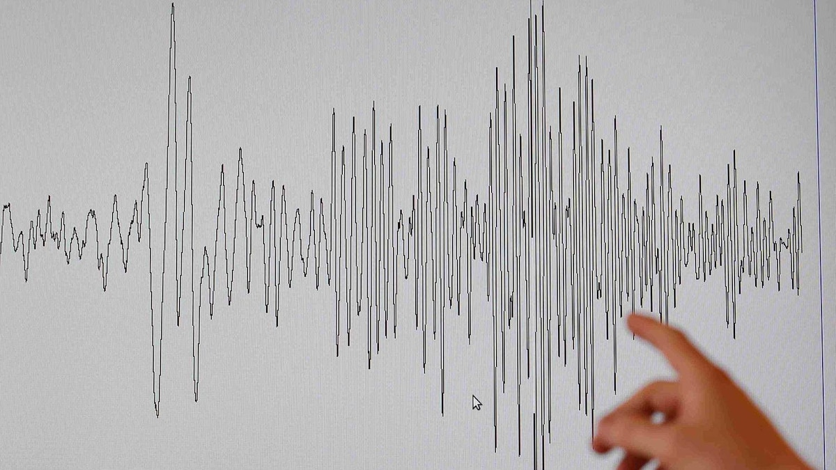 A technician at the French National Seism Survey Institut points at a graph registered today during a major earthquake that hit Japan