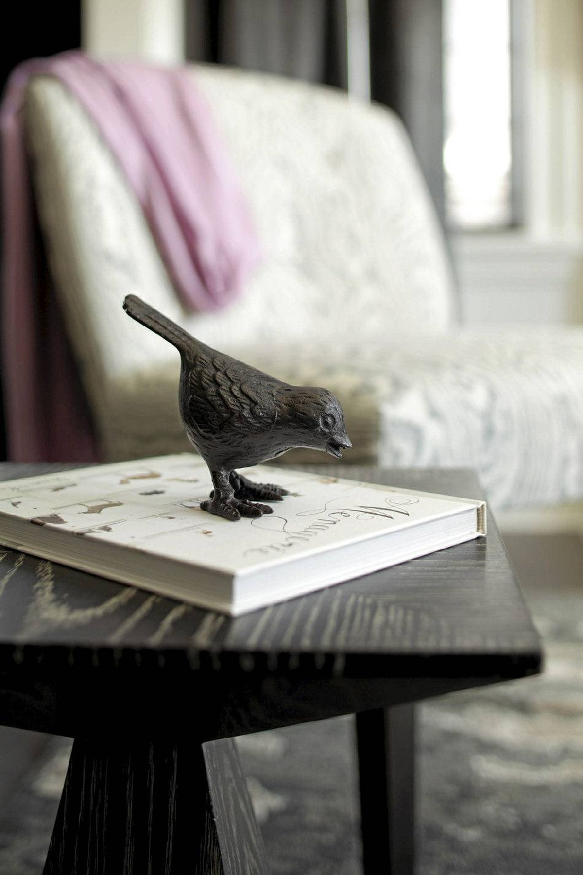 Bird statue on the coffee table. A cast concrete fireplace facade with a simple profile achieves a delicate balance: The material's weight echoes the home's substance while its finish accentuates the muted elegance of the room's furnishings.