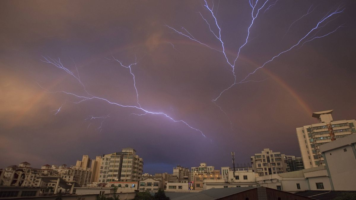 A rainbow is seen in the sky as lightning strikes after a rainstorm in Haikou, Hainan province, May 13, 2012. Picture taken May 13, 2012.