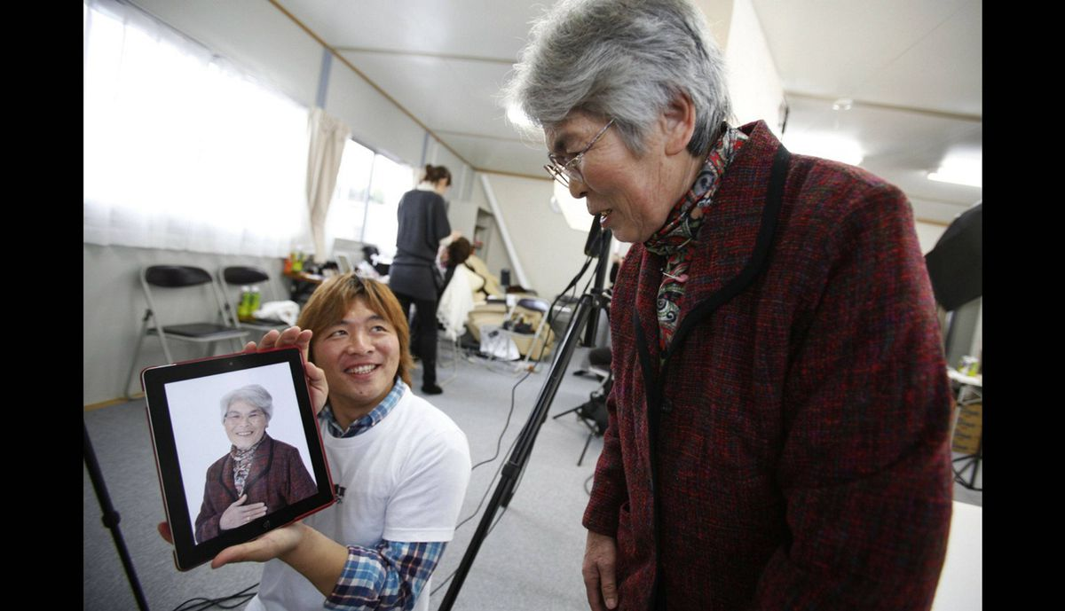 Photographer Kenichi Funada (L) shows Tsugiko Miyajima her portrait on his iPad after taking part in the 3.11 Portrait ProjectThe project was conceived by photographer Nobuyuki Kobayashi who takes portraits of Japan's earthquake survivors. The portraits are then sent to schoolchildren from non-disaster areas, who frame the portraits and send them back to the survivors along with personal messages of support.
