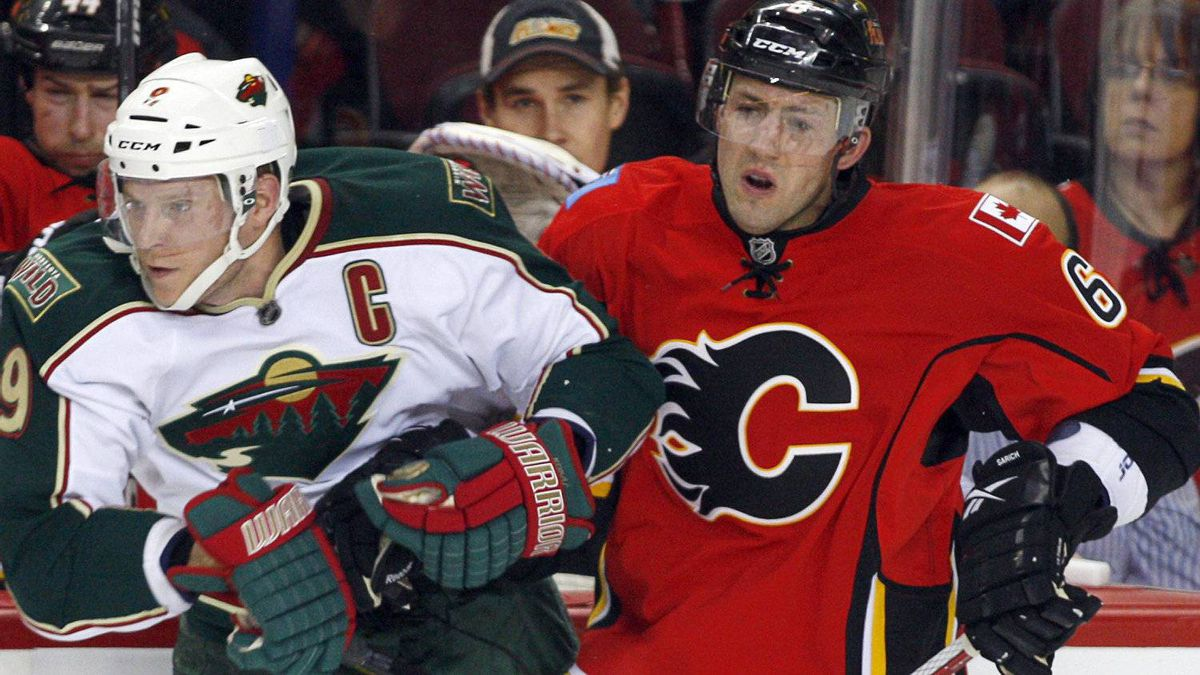Minnesota Wild's Mikko Koivu, left, of Finland, checks Calgary Flames' Cory Sarich during first period NHL hockey action in Calgary, Alta., Saturday, Jan. 7, 2012. The Flames won 3-1. THE CANADIAN PRESS/Jeff McIntosh