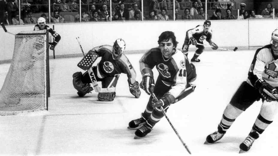 Winnipeg Jets defenceman Serge Savard and Toronto Maple Leaf John Anderson chase the puck in the Jet end on Jan. 27, 1982, in Toronto.