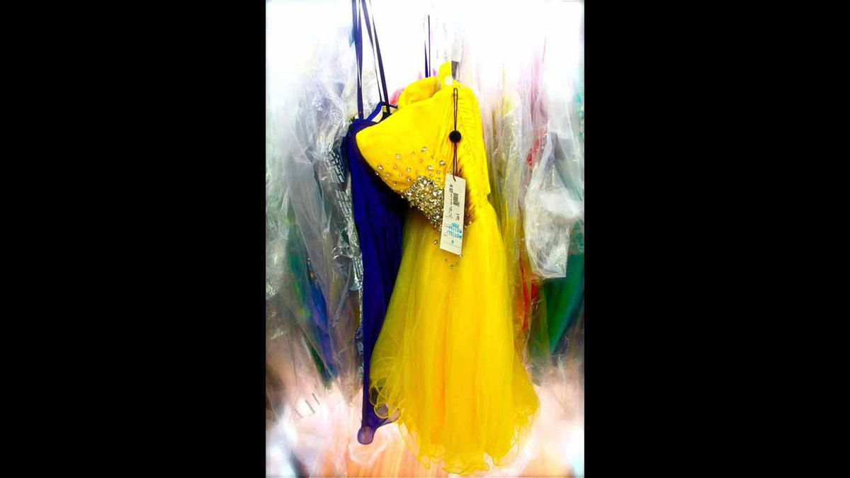 A bright vellow prom dress floats against a backdrop of swirling splashes of colour in this abstract photo taken on April 28, 2012, in a mid-town Toronto boutique. by Julie Enfield