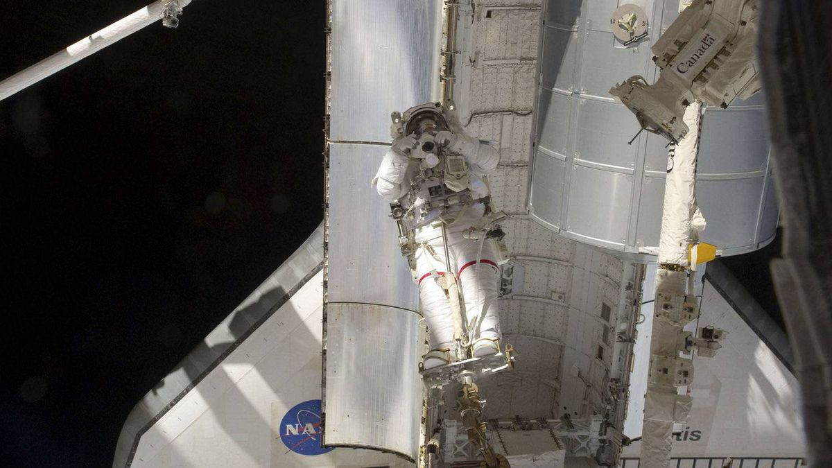 NASA astronaut Mike Fossum, restrained on the end of the space station remote manipulator system or Canadarm2, takes a picture in front of the space shuttle Atlantis during the final spacewalk of a shuttle mission in this photo taken July 12, 2011.