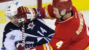 Calgary Flames' Jay Bouwmeester (R) pushes Winnipeg Jets' Tim Stapleton in front of the net during the second period of their NHL hockey game in Calgary, Alberta March 9, 2012. REUTERS/Todd Korol