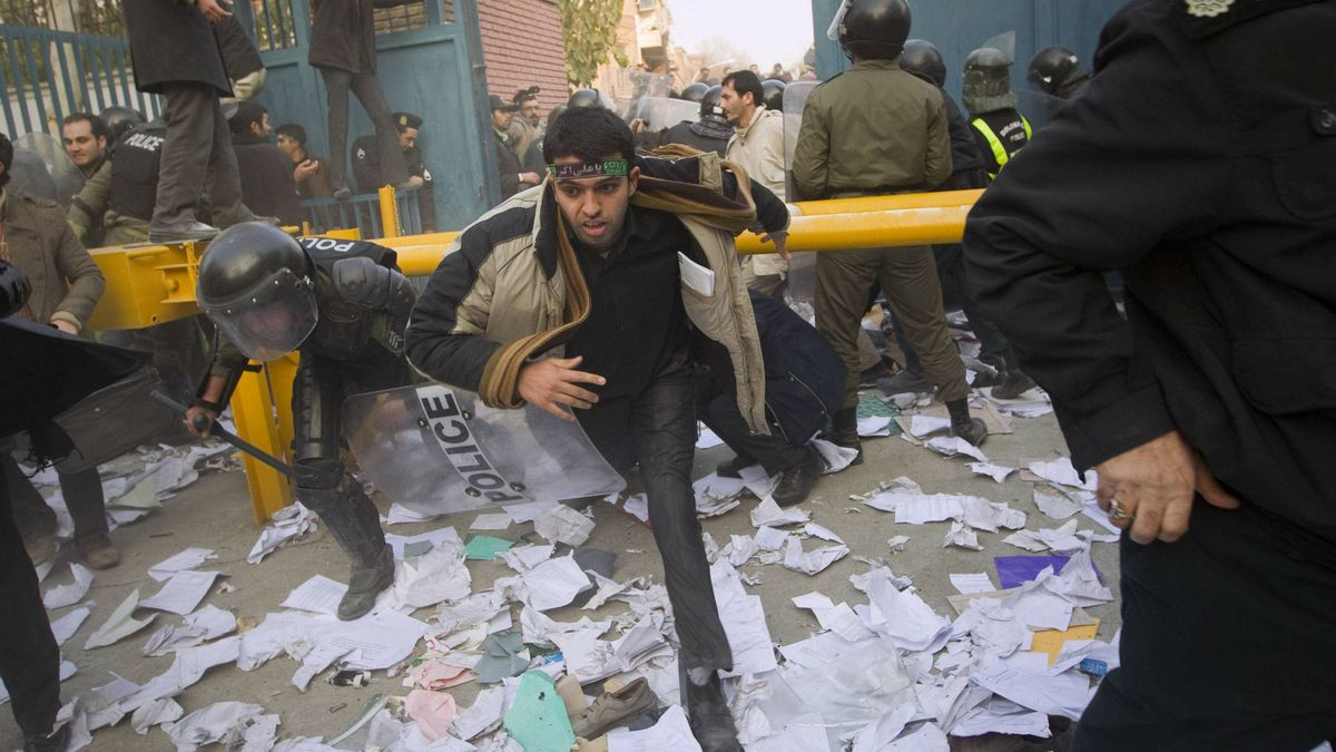 Police chase protesters as they enter the gate of the British embassy in Tehran on Tuesday. Dozens of young Iranian men entered buildings inside the British embassy compound, throwing rocks, petrol bombs and burning documents looted from offices, Iranian news agencies reported.