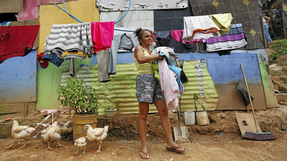 Maria Colmenares does her laundry outside her shack in Las Mayas.