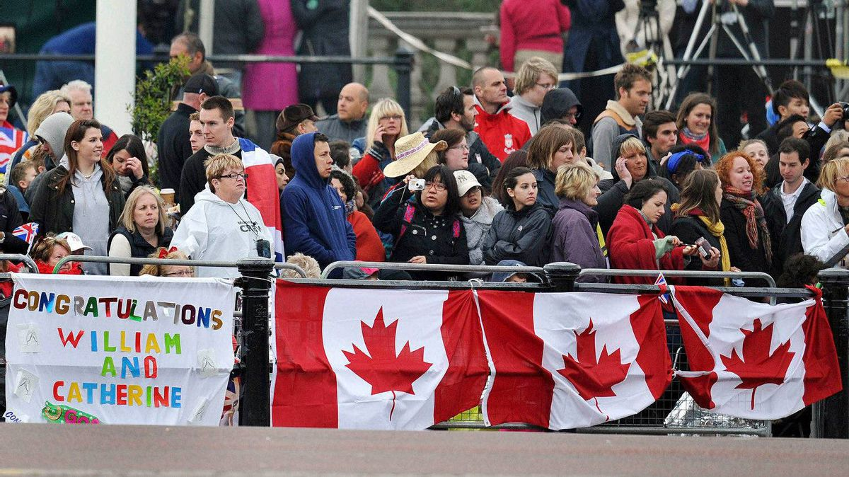 Royal supporters stand behind national flags of Canada near Buckingham Palace in London April 29, 2011.