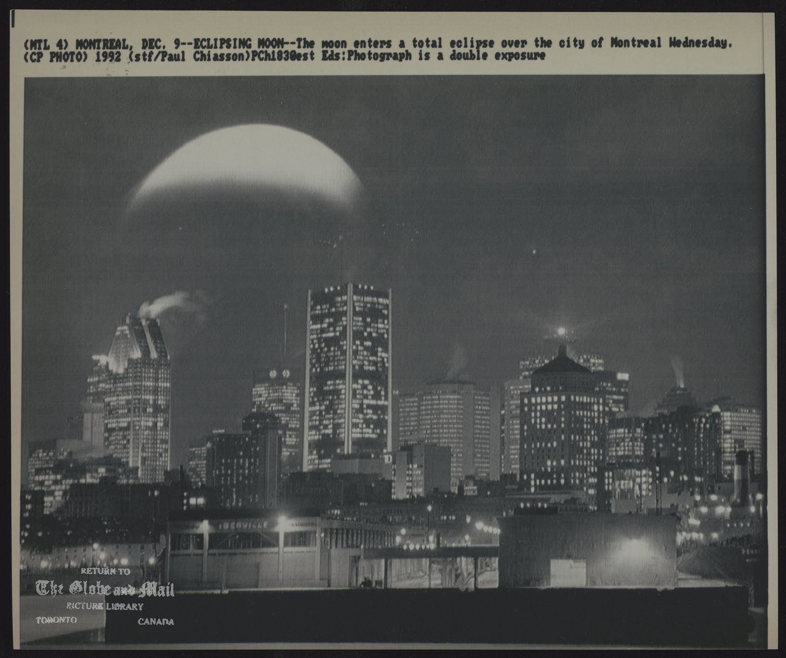 ECLIPSE (MTL 4) MONTREAL, DEC. 9--ECLIPSING MOON--The moon enters a total eclipse over the city of Montreal Wednesday. Eds: Photograph is a double exposure (CP Photo) 1992 (stf/Paul Chiasson) PCh1830est
