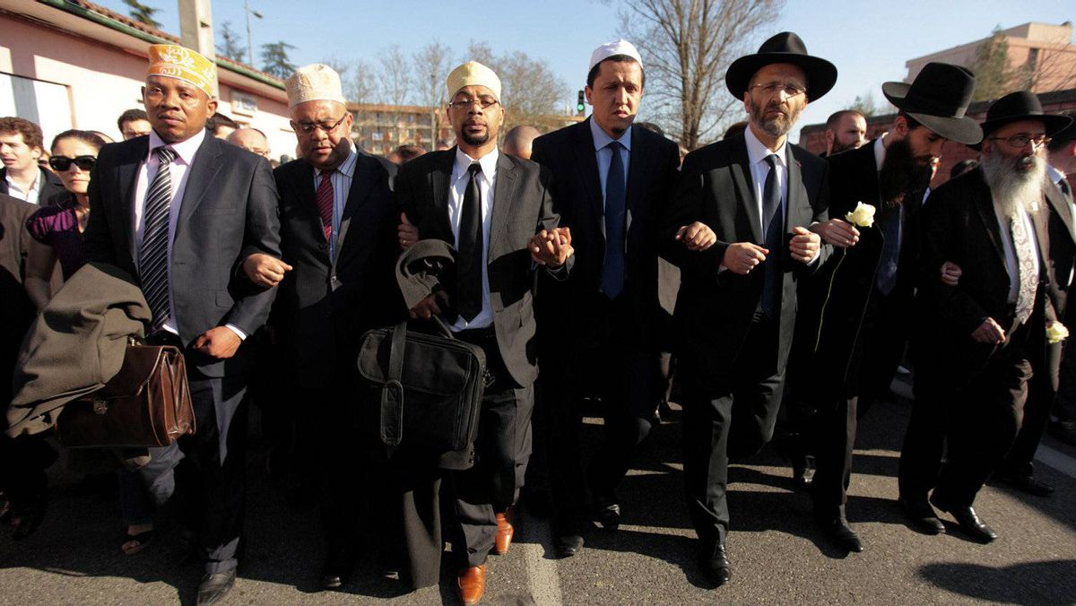 Jewish and Muslim leaders link arms in a silent march to honour the victims of a shooting at the Ozar Hatorah school, where a rabbi and three children were killed in Toulouse March 25, 2012.