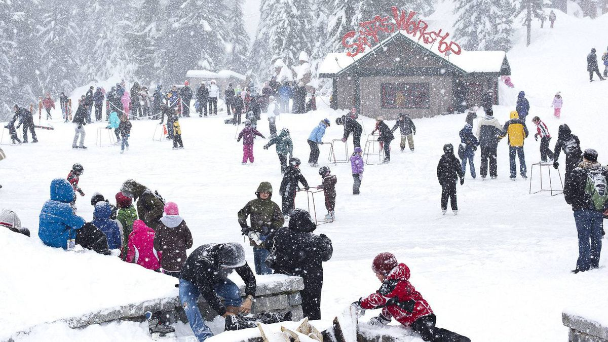 The skating pond atop Grouse Mountain is filled with people as snow billows down on top of the mountain on December 20, 2010, Vancouver.