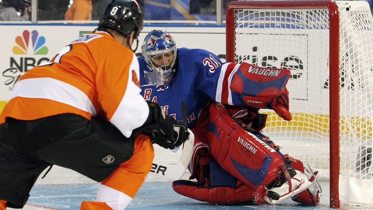 Brad Marsh, left, of the Philadelphia Flyers alumni team, launches a wrist-shot at goalie Dan Blackburn, of the New York Rangers alumni team. (AP Photo/Tom Mihalek)