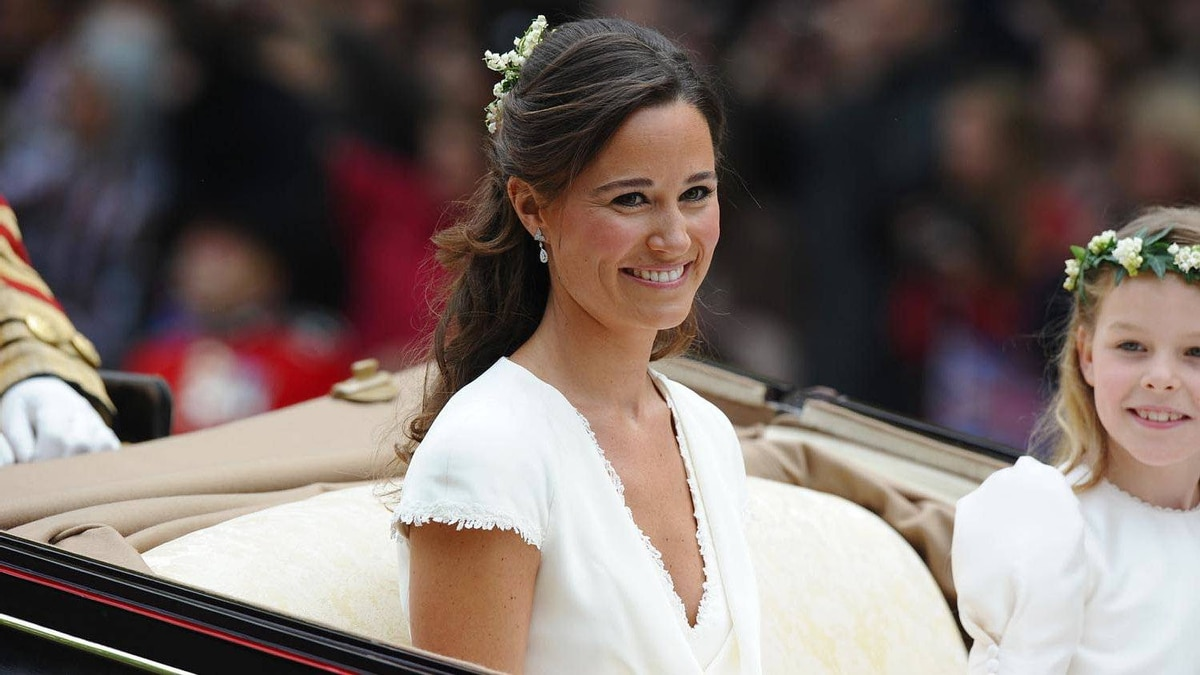 Maid of honour Philippa Middleton smiles as the travels in a Semi-State Landau in London after the wedding service for Britain's Prince William and Kate, Duchess of Cambridge, on April 29, 2011.