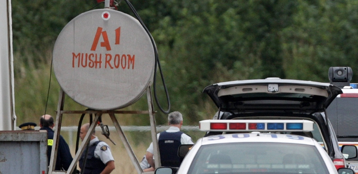 Police officers stand at the scene after three people were overcome by an unknown substance and died at a mushroom farm in Langley, B.C., on Friday September 5, 2008.