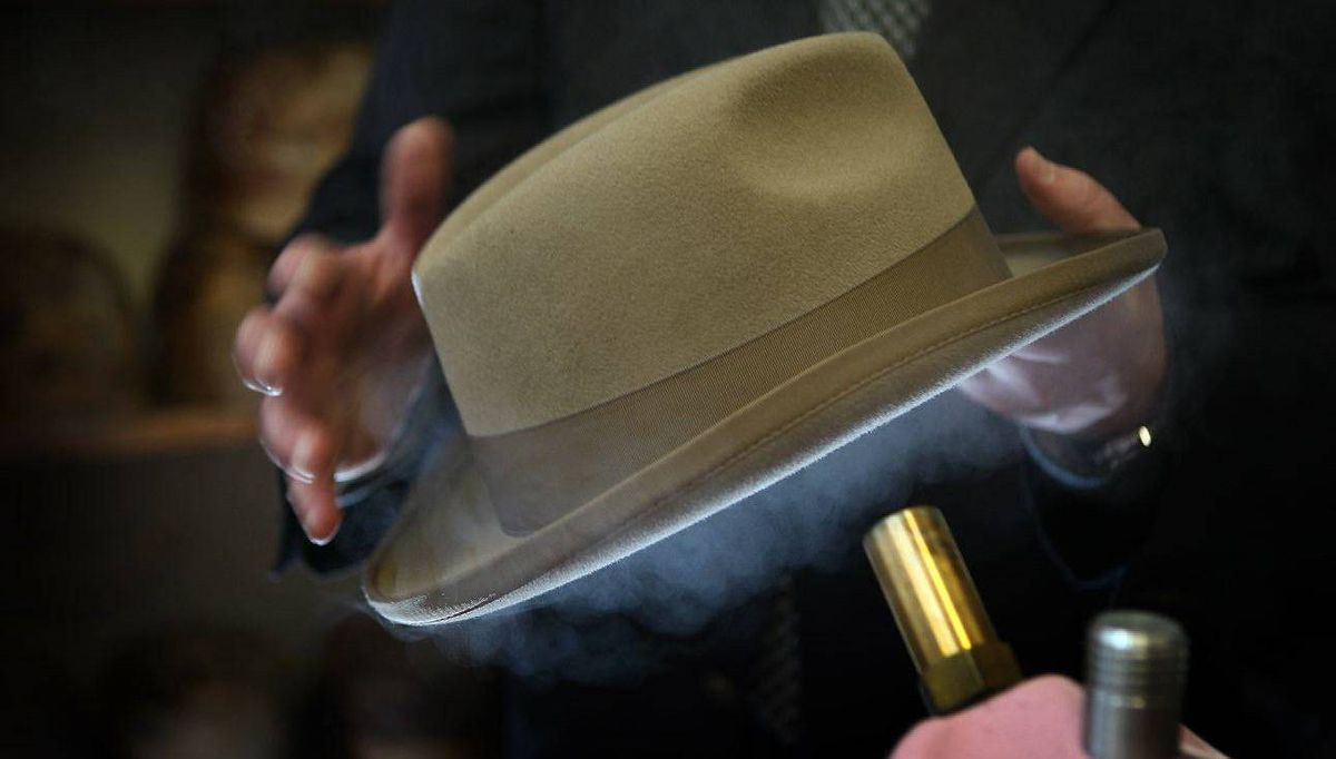 Retail manager Andrew Baselgia steams a Homburg to retain its shape.