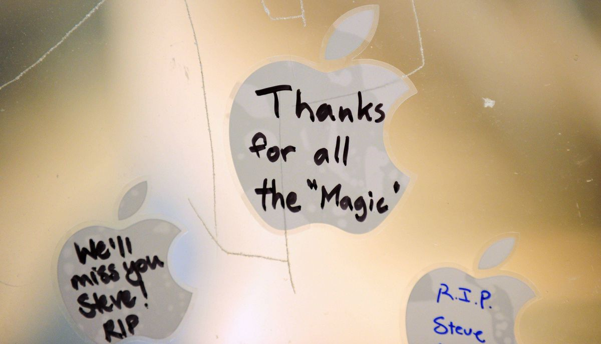 Messages on Apple stickers are left on the window of the Apple store in Pasadena, California, October 5, 2011.