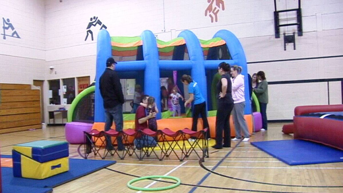 Kids play in a bouncy castle while coach and parents watch. It's one of several pieces of equipment set up in a school gymnasium.