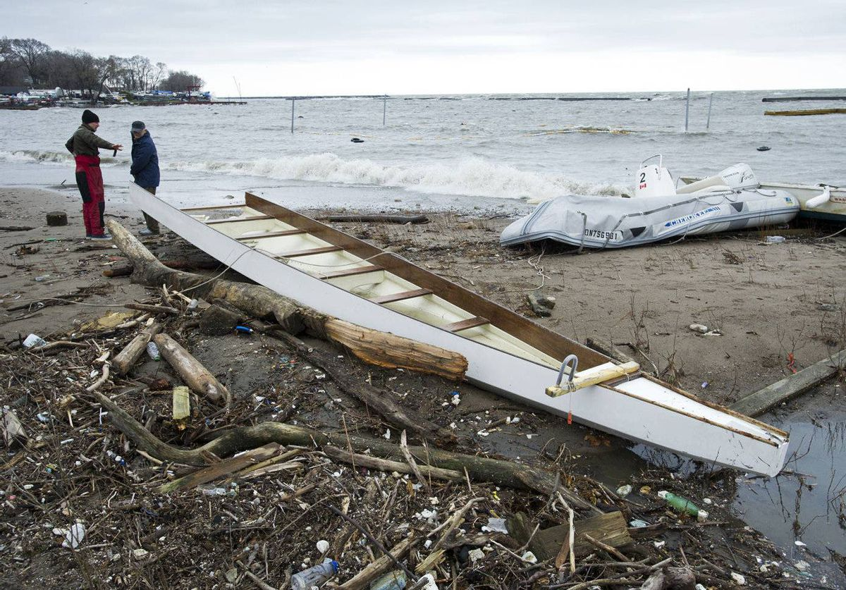Boaters Ian Howes, left, and Bill Burek survey the damage to several boats along the shores of Lake Ontario near Sunnyside Park in Toronto, Ont. Wind gusts of up to 90km per hour downed power lines, damaged buildings and wrecked boats.