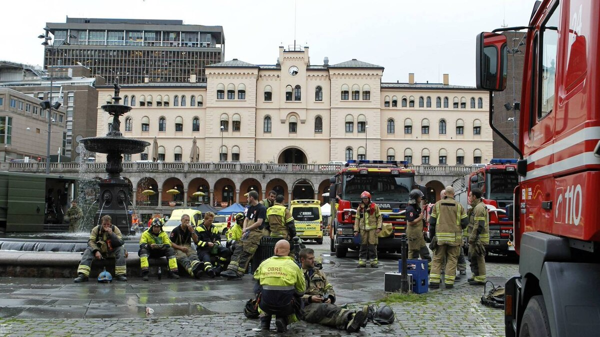Firefighters and rescue workers rest after tending to victims of a bomb blast which took place outside the Norvegian Prime Minister's office in Oslo, on July 22, 2011.