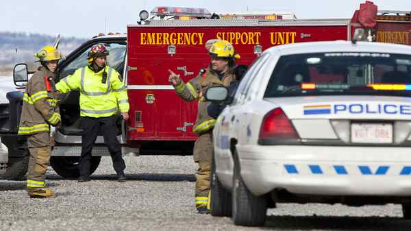 Emergency crews tend to the landing area of Kananaskis Mountain Helicopters west of Calgary after one of its helicopters crashed on Friday afternoon.