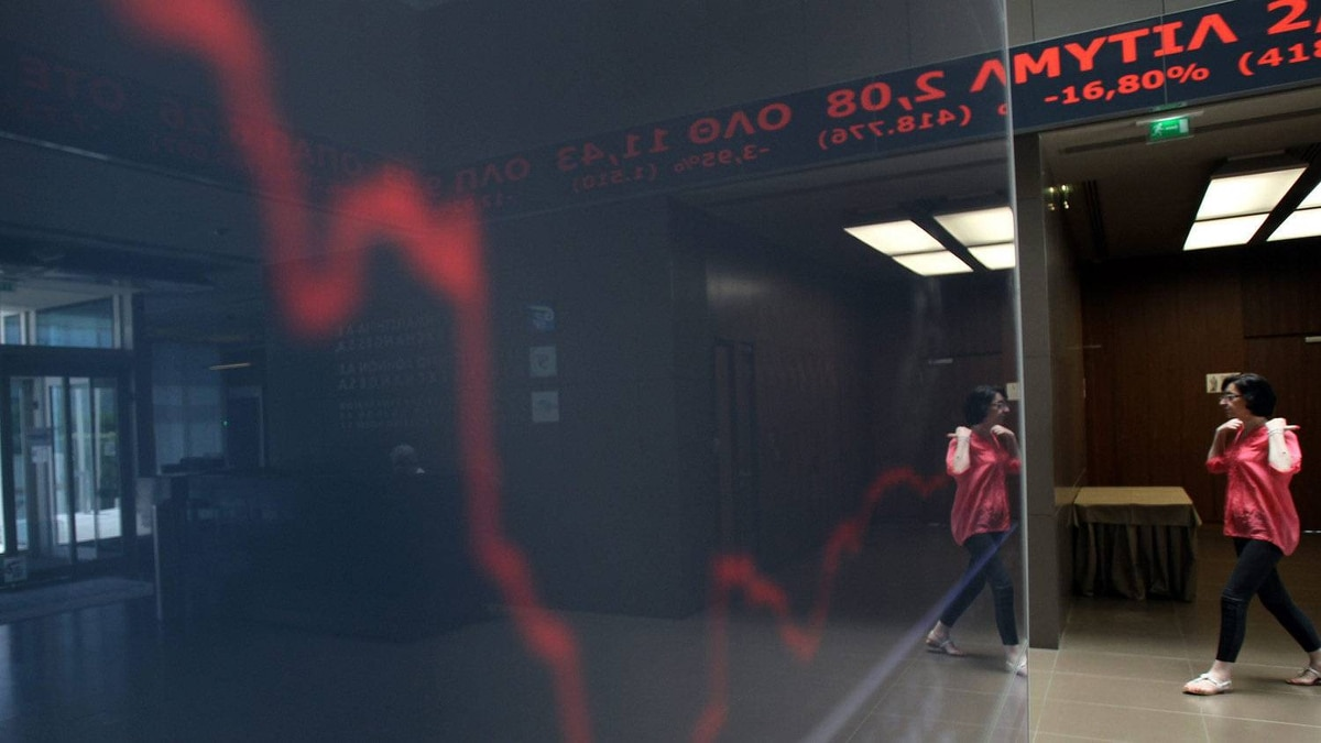 A woman passes in front of chart with the stock prices at the Greek Stock Exchange in Athens on Monday, May 7. In reaction to the election, Greek bonds tumbled more than €3, considered a huge move in the fixed-income market, and yields soared to a punishing 21.87 per cent, up nearly two full percentage points on the session.