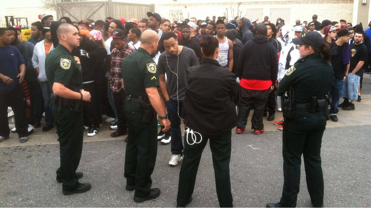 Orange County Sheriff's deputies move the crowd back after an announcement Friday morning, Feb. 24, 2012 that a shoe giveaway was cancelled at the Foot Locker at Florida Mall, in Orlando, Fla.