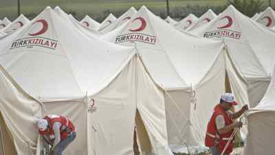 Turkish Red Crescent workers are seen in an almost completed new refugee tent compound in Boynuyogun, Turkey, near the Syrian border, Saturday, June 11, 2011.