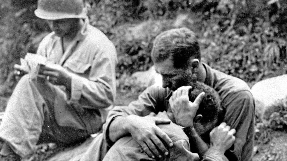 An American infantryman, his buddy killed in action in the Korean War, weeps on the shoulder of another GI somewhere in Korea, in this Aug. 28, 1950 file photo.