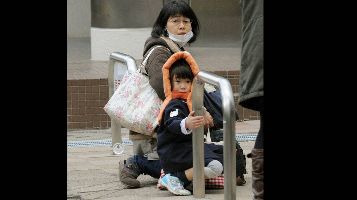 A mother and child crouch on a street in Tokyo as an earthquake hits.